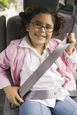 Girl fastening seatbelt in backseat of car — Stock Photo