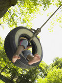 Barefoot girl on tire swing — Stock Photo