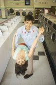 Couple dancing in a laundromat — Stock Photo