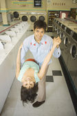 Couple dancing in a laundromat — Stok fotoğraf
