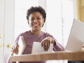 Middle-aged woman smiling for the camera at her desk — Stock Photo