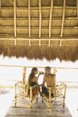 Couple drinking beer at a table underneath thatch roof — Stok fotoğraf