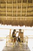 Couple drinking beer at a table underneath thatch roof — ストック写真