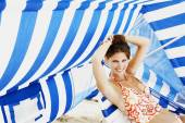 Young woman sitting under beach sun shade — Stok fotoğraf