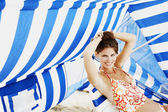 Young woman sitting under beach sun shade — Stock Photo