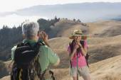 Senior man taking a picture of his wife on a hike — Stock Photo