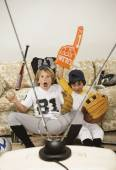 Two boys in sports gear watching television — Stock Photo