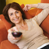Hispanic woman pointing remote control — Foto de Stock