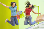 Multi-ethnic teenage girls jumping with shopping bags — Stock Photo