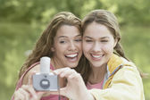 Women taking snapshots in a forest — Stock Photo