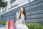 African woman with shopping bags talking on cell phone — Stok fotoğraf