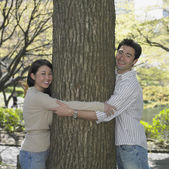 Asian couple hugging tree in park — Stock Photo