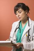 Female doctor writing notes — Stock Photo