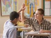 Students high fiving in class — Stock Photo