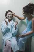 Two young girls applying facial masks in bathroom — Stock Photo