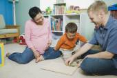Pregnant parents playing with young son — Stock Photo