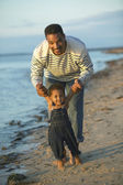 African father helping toddler walk on beach — Stockfoto