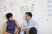 Two businesspeople sitting in front of whiteboard wall — 图库照片