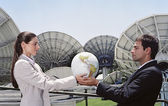 Hispanic businesspeople holding globe in front of satellite dishes — Stock Photo