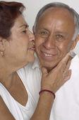 Senior Hispanic woman kissing husband — Stock Photo