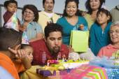 Hispanic man blowing out candles on birthday cake with family — Stock Photo