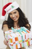 Hispanic woman wearing Santa hat and holding out gift — Stock Photo