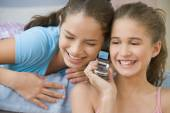 Hispanic sisters using same cell phone — Stock Photo