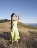 Woman using telescope to view distant hills — Stock Photo