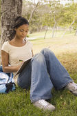 Young African woman with backpack leaning on tree and writing — Stock Photo