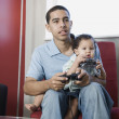 Young African father playing video games with baby on lap — Stock Photo #52030863
