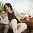 African mother and young son smiling next to canoe — Stock Photo #52031037