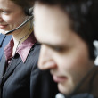 Three businesspeople talking on headsets — Stock Photo #52031187