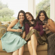 Three women sitting on couch with wine glasses — Stock Photo #52031371