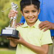 Hispanic girl holding golf trophy — Stock Photo #52031919