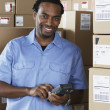 Male African warehouse worker scanning packages — Stock Photo #52032393