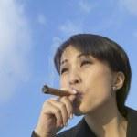 Asian businesswoman smoking cigar — Stock Photo #52033325