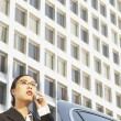 Asian businesswoman using cell phone next to car — Stock Photo #52033653