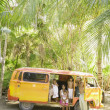 Family posing for the camera with van in tropical setting — Stock Photo #52033733