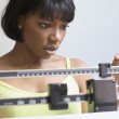 Woman weighing herself on scale — Stock Photo #52033775