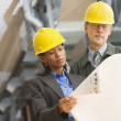 Two businesspeople in hard hats looking at blueprints — Stock Photo #52033793