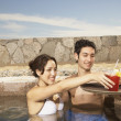 Couple being served drinks in a resort pool — Stock Photo
