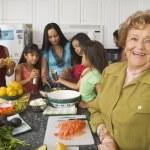 Large Hispanic family in kitchen preparing food — Stock Photo #52034703