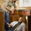 African couple installing kitchen sink — Stock Photo #52035021