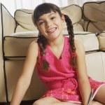 Young girl sitting on floor doing homework — Stock Photo #52035077