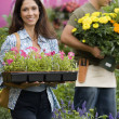 Hispanic woman carrying flowers at plant nursery — Stock Photo #52035339