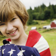 Girl wrapped in American flag on farm — Stock Photo #52035395