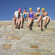 Group of senior women in bathing suits sitting on stone wall — Stock Photo