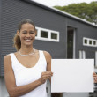 Mixed Race woman holding blank paper in front of house — Stock Photo #52036117