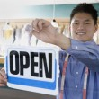Asian drycleaner putting up open sign — Stock Photo #52036605