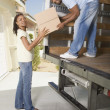 African man handing box to woman out of moving truck — Stock Photo #52036785